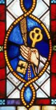 stained glass depicting hands clasped